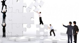 Empresarios emprendedores construyendo un puzzle gigante haciendo referencia a las modificaciones en la ley de emprendedores