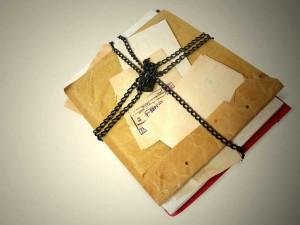 Fotografía de unos papeles y carpetas rodeados de una cadena con un candado haciendo referencia al secreto de sumario