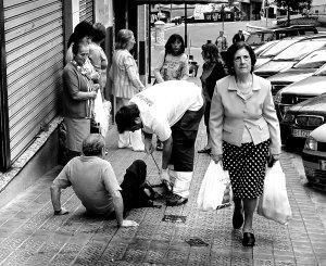Una persona mayor que se ha caido en la calle y otros ciudadanos están a su alrededor para atenderle. La imagen guarda relación con las indemnizaciones por los daños de las caidas en la calle