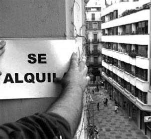 """Fotografía de un propietario de una vivienda colocando en su valcon un cartel de """"Se Aquila"""""""