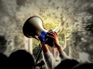 Fotografía de una persona que sujeta un megáfono junto a otro grupo de personas que le acompaña. La imagen refleja las nuevas medidas sociales como la de protección a los trabajadores