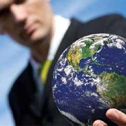 Fotografía de un hombre con la bola de mundo en su mano izquierda haciendo referencia a la expansión del arbitraje en el comercio internacional