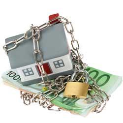 Imagen de una casa atada con una cadena y un candado a un puñado de billetes. La imagen está relacionada con El registro de sentencias en el impago del alquiler