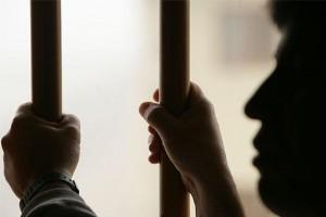 Fotografía de una hombre preso que sujeta con sus dos manos los barrotes de la celda. La imagen refleja la situación con la prisión permanente revisable