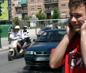 Fotografía de un ciudadano granadino tapandose los oidos en la calle mientras circula por el ruido de las calles