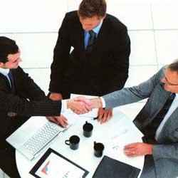 Fotografía de tres hombres vestidos de traje, de los cuales, dos están sentados y dándose a mano y el tercero de pie realizando la función de mediador. La imagen se refiere a la mediación como alternativa al concurso de acreedores