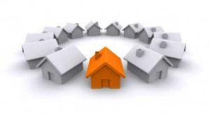 La imagen muestra unas casas hechas por ordenador que forman un circulo entre ellas. todas las casas son blancas menos una que es de color naranja. La imagen está relacionada con el impago en las cuotas de la comunidad de vecinos