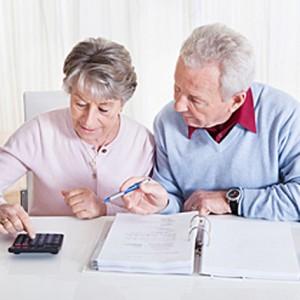 Dos ancianos sentados y realizando sus cuentas de la jubilación