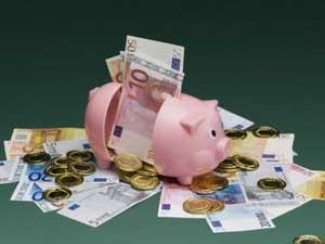 La imagen muestra la ucha de un cerdo rota con varios billetes y monedas de euro saliendo de ella. La imagen está relacionada con la tarifa plana en la seguridad social