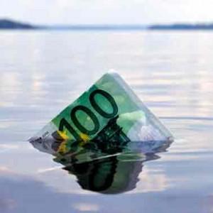 Un billete de cien euros flotando en el agua de un lago en referencia a la reforma de los acuerdos de refinanciación en el preconcurso