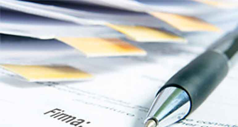 Una serie de archivos de papel y sobre ellos un bolígrafo en relación con la norma para reducir las trabas administrativas a las empresas