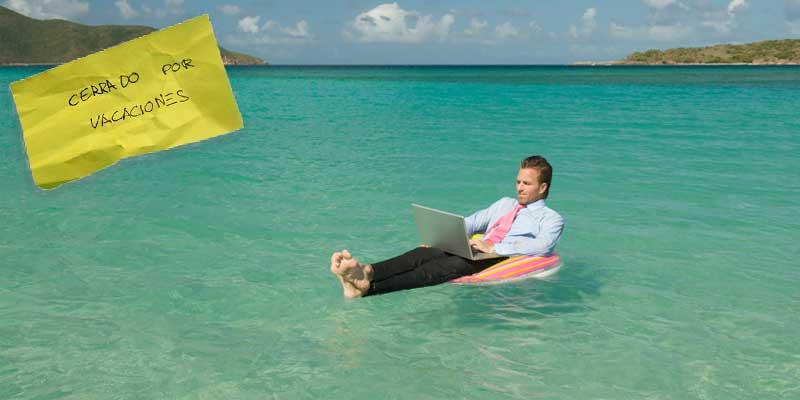 Fotografía de un trabajador disfrutando de sus vacaciones em la playa sobre una colchoneta en el mar, vestido de oficina y con el portatil encima