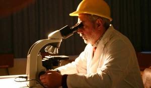 un investigador mirando a través de un microscopio y con un sombrero de obra en relación a las bonificaciones por contratar a personal investigador