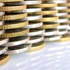 Varias monedas colocadas unas sobre las otras en relación a la retribución del administrador en el impuesto de sociedades