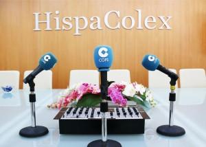 """Tres microfonos de la emisora de radio COPE y de fono la pared con unas letras """"HispaColex"""" en relación al programa de radio """"Granada Empresas"""" que realizan en común"""