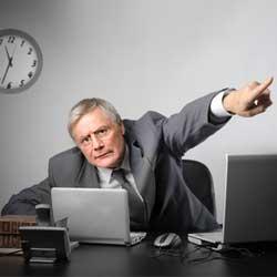 Un empresario sentado en su mesa de trabajo y señalando con el dedo hacia la calle en señal del despido