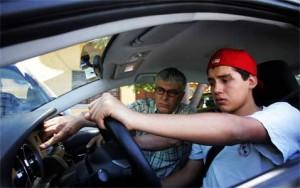 Un hijo menor conduciendo junto a su padre como copiloto. La imagen está relacionada con la póliza de seguro
