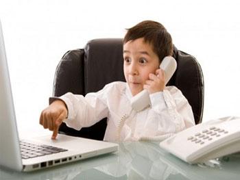 Un niño vestido de traje y trabajando en su oficina con el ordenador y teléfono en referencia a las ayudas de Bono de Empleo Joven para empresas