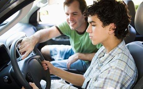 Un padre enseñando a conducir a su hijo. Un hecho que puede suponer un delito contra la seguridad vial