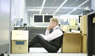Un trabajador que acaba de ser despedido y se encuentra con postura pensativa sentado en el suelo de la oficina junto a unas cajas